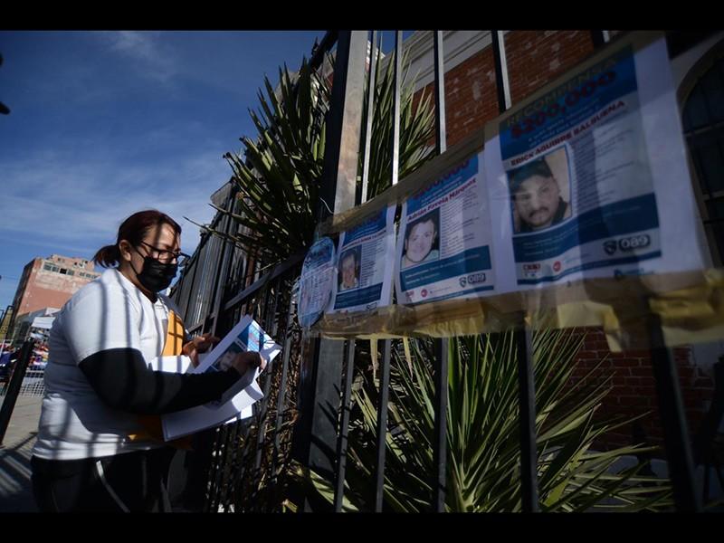 Familiares colocan pesquisas de desaparecidos durante el acto celebrado frente al Muref.